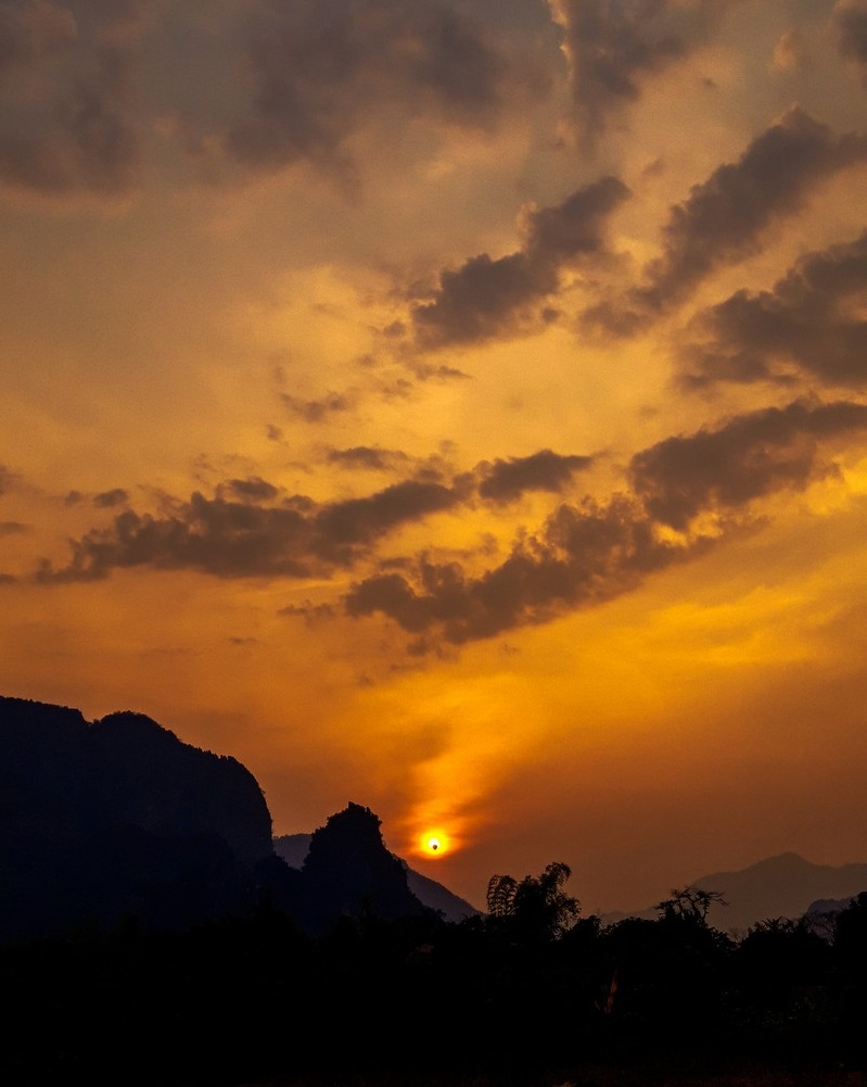 After exploring Vang Vieng caves on my own by bicycle, I met this local guy and we went together at this unexplored spot to watch the sunset: Tha Heua.